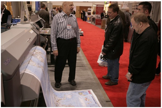 Company president John Mitchell (left) talks to customers at Print World 2010